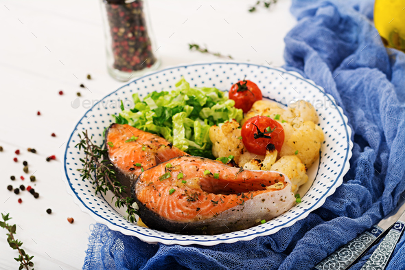 Dietary menu. Baked salmon steak with cauliflower, tomatoes and herbs - Stock Photo - Images