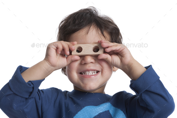 Two year old boy looking through the holes of a block - Stock Photo - Images