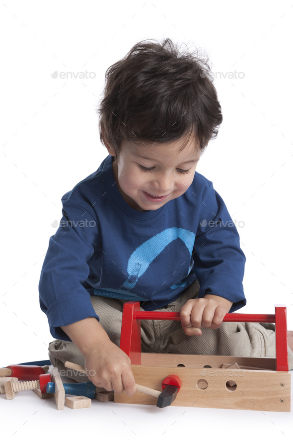 Two year old boy is playing with wooden tools - Stock Photo - Images