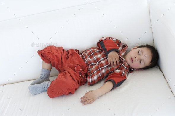 Two year old boy sleeping on a couch - Stock Photo - Images