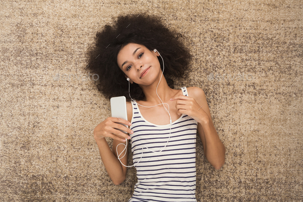 Happy young woman in headphones on floor - Stock Photo - Images
