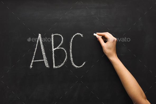 Woman writing abc on black chalkboard - Stock Photo - Images
