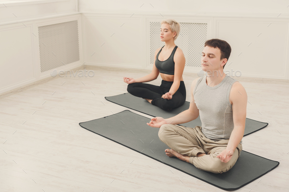 Young couple meditating together in studio - Stock Photo - Images