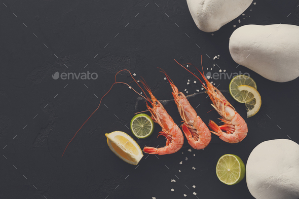 Shrimps with lemon and stones on black background - Stock Photo - Images