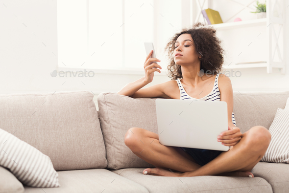 Young girl with laptop messaging on mobile - Stock Photo - Images