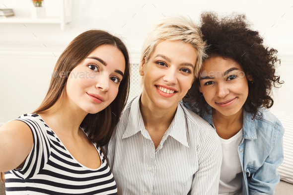 Happy friends taking selfie at home - Stock Photo - Images