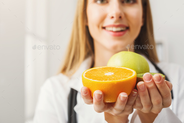 Smiling nutritionist woman with fruit at office - Stock Photo - Images