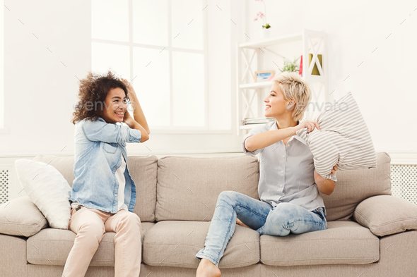 Two young women having pillow fight on sofa - Stock Photo - Images