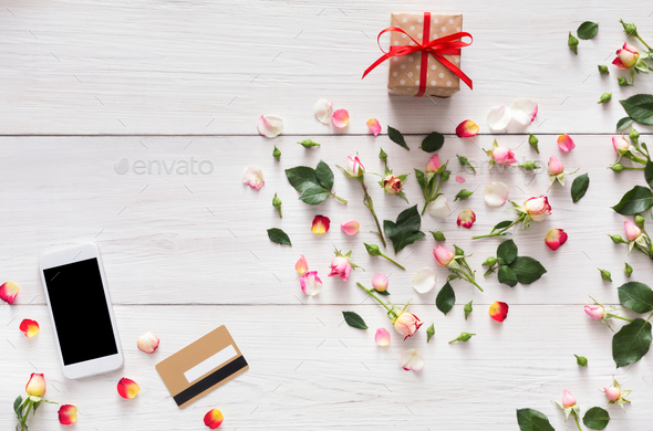 Phone screen with copy space on white wood, rose flowers heart, gift box, credite card - Stock Photo - Images
