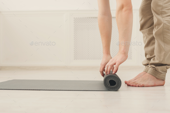 Rolling up fitness mat for exercise copy space - Stock Photo - Images