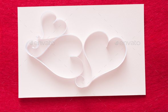 Valentine background with handmade paper heart shapes decoration on white shit of paper on red felt - Stock Photo - Images