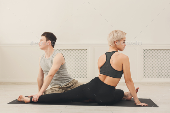Young couple practicing yoga together in studio - Stock Photo - Images