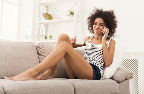 Young woman at home talking on mobile phone - Stock Photo - Images