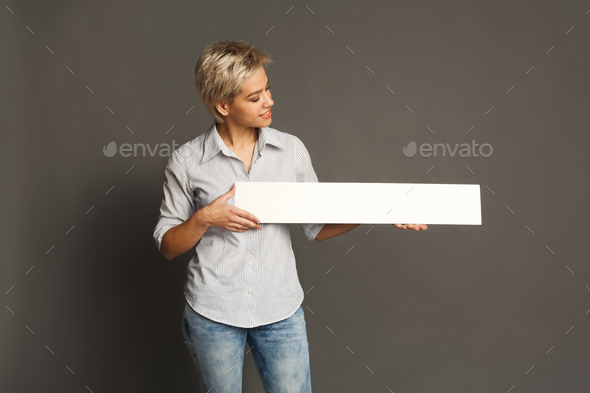 Young woman holding blank white banner - Stock Photo - Images