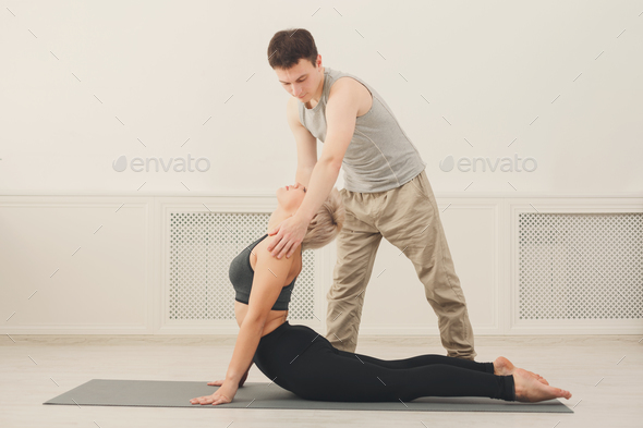 Young woman with yoga instructor in fitness club - Stock Photo - Images