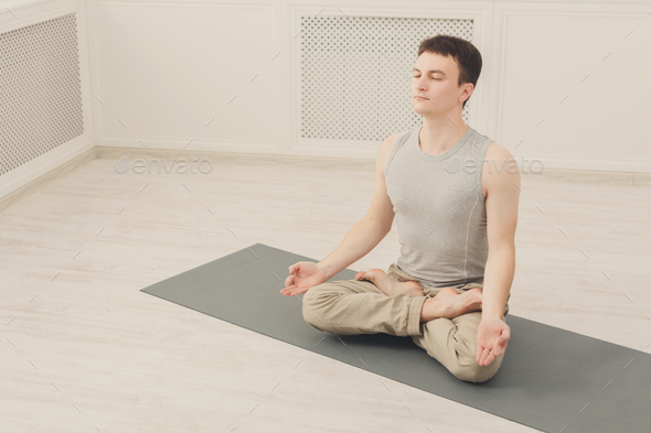 Young man in yoga class, relax meditation pose - Stock Photo - Images