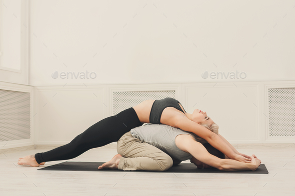 Young couple practicing acroyoga on mat together - Stock Photo - Images
