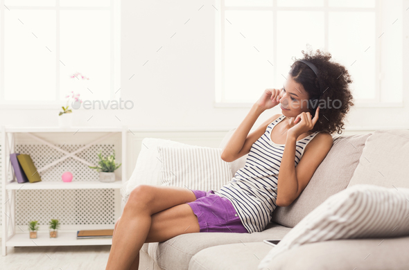 Happy young woman in headphones on beige couch - Stock Photo - Images
