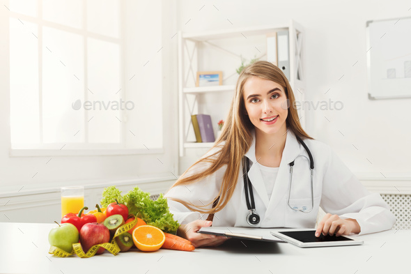 Female nutritionist working on digital tablet - Stock Photo - Images