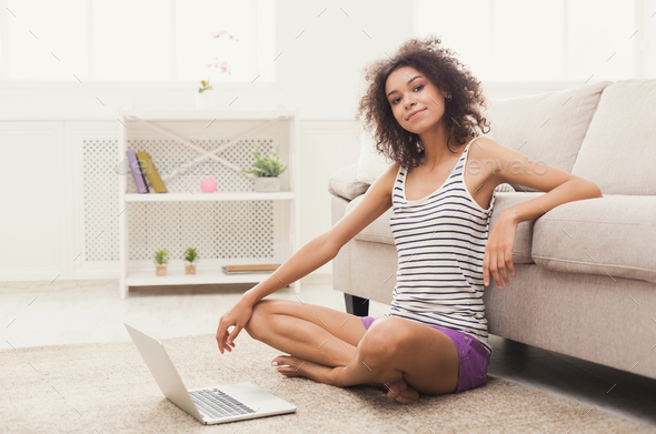 Young girl with laptop sitting on floor - Stock Photo - Images