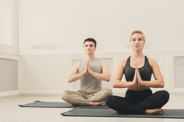 Young couple practicing yoga sitting in padmasana - Stock Photo - Images
