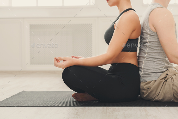 Young couple meditating together, back to back - Stock Photo - Images