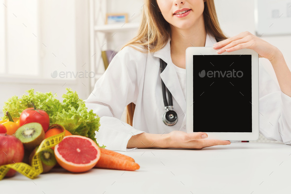 Doctor nutritionist and holding digital tablet - Stock Photo - Images