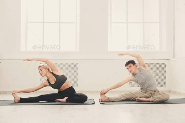 Fitness couple stretching at white background - Stock Photo - Images