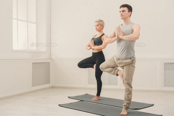 Couple training yoga in tree pose. - Stock Photo - Images