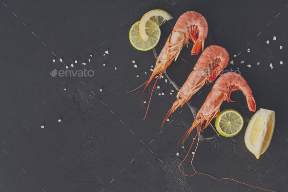 Shrimps with salt and lemon on black background - Stock Photo - Images