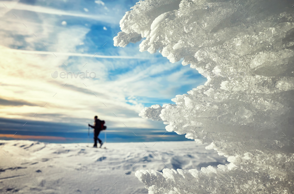 Ice formations at sunset, cross-country skier silhouette in dist - Stock Photo - Images