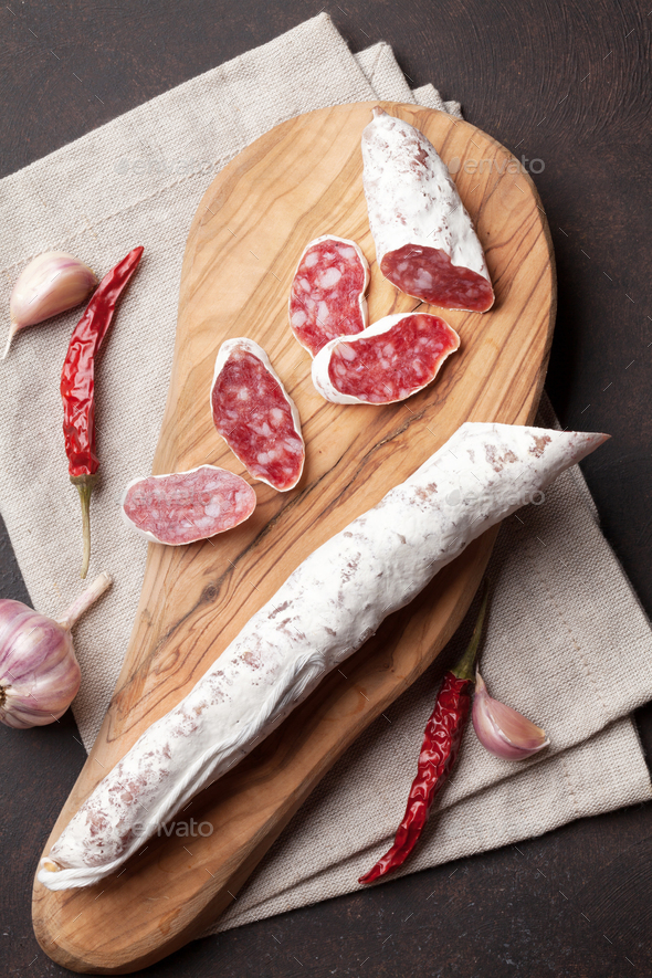 Sliced salami on cutting board - Stock Photo - Images