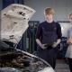 the Young Mechanic Works in a Car-care Center, the Person Communicates with the Automobile Owner - VideoHive Item for Sale