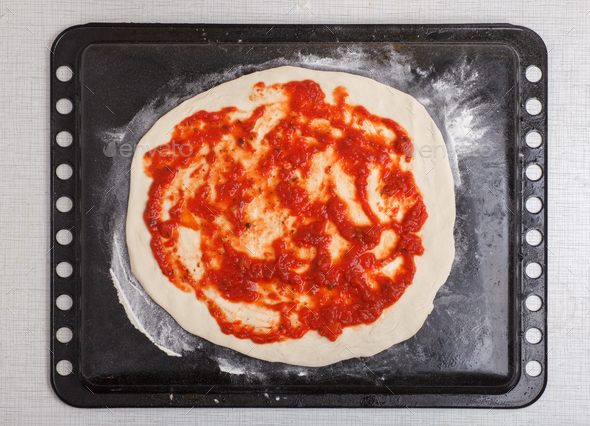 round ra pizza with tomato sauce on baking tray - Stock Photo - Images