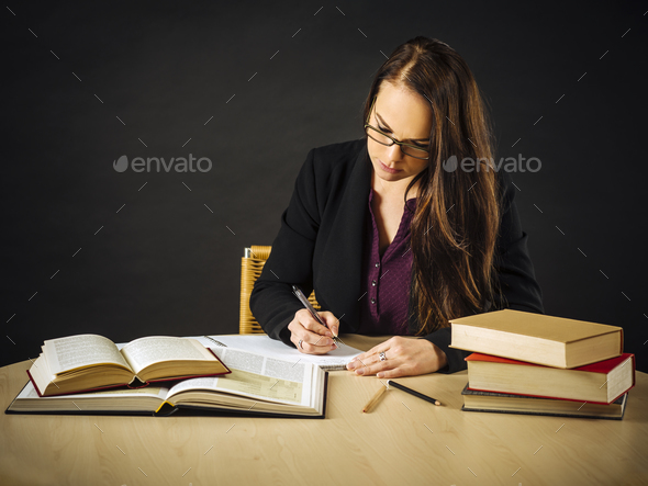 Attractive teacher sitting at her desk writing - Stock Photo - Images