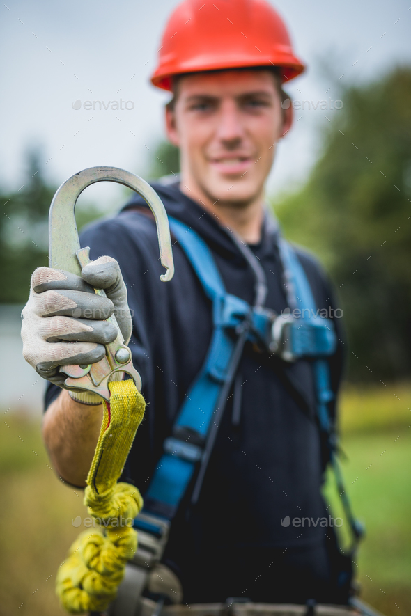 Technician man in hardhat showing safety hook. - Stock Photo - Images