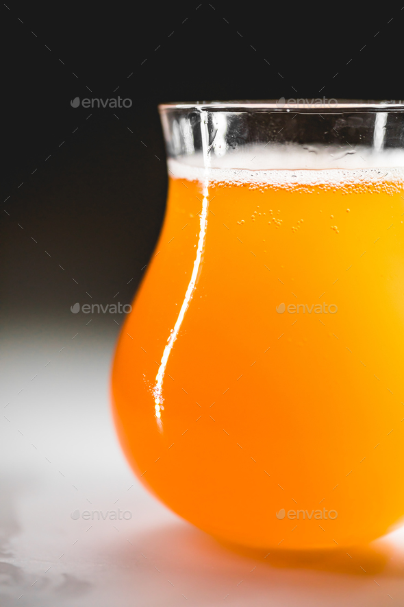 Close-up glass of homebrewed rhubarb beer with white foam. - Stock Photo - Images