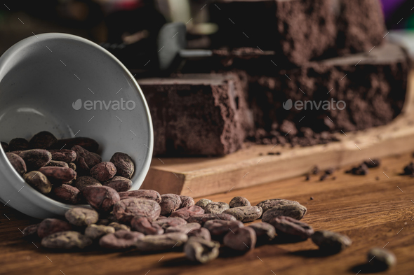 Arrangement of cocoa beans and chocolate bars on wooden surface. - Stock Photo - Images