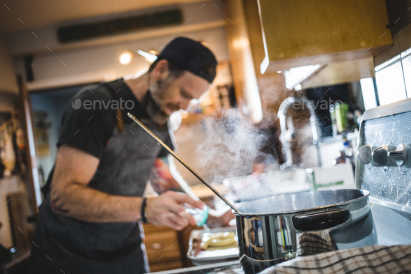 Unrecognizable person parboiling and salting pretzel. - Stock Photo - Images