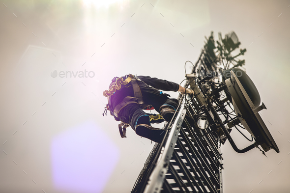 Telecom Worker Climbing Antenna Tower with Harness and Tools - Stock Photo - Images