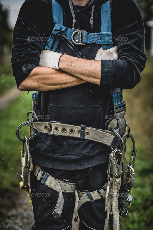 Technician in uniform with harness standing with arms crossed. - Stock Photo - Images