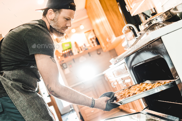 Man taking pan with pretzels - Stock Photo - Images