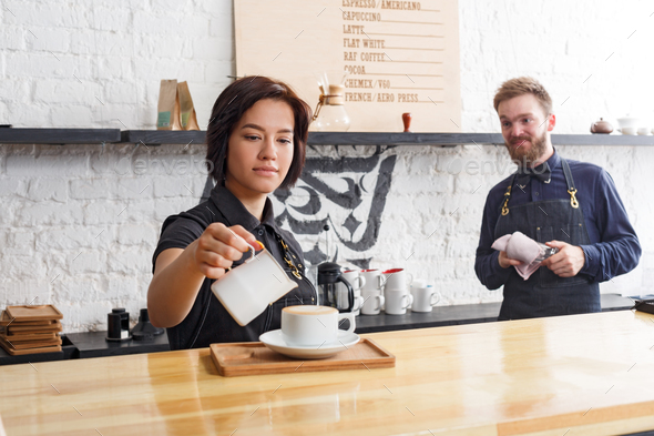 Male and female bartenders brewing fresh coffee at cafe interior - Stock Photo - Images