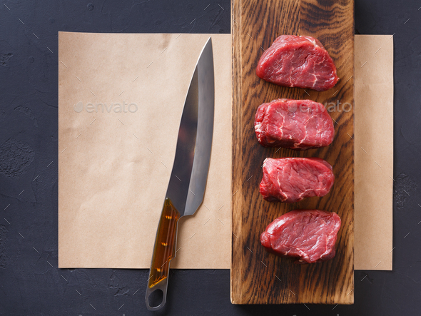 Raw beef filet mignon steaks on wooden board and craft papper - Stock Photo - Images