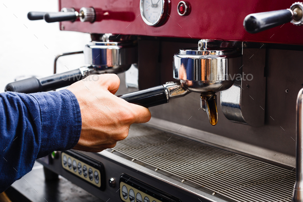 Closeup of barmen hand brewing espresso in professional coffee machine - Stock Photo - Images
