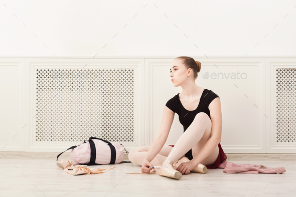 Ballerina puts on pointe ballet shoes, - Stock Photo - Images