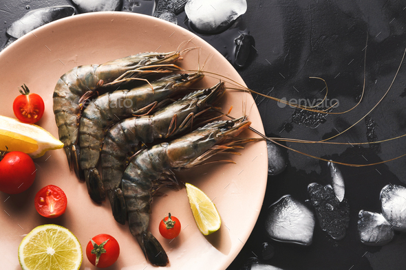 Raw shrimps with lemon on black background - Stock Photo - Images