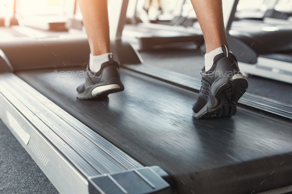 Man's feet on treadmill in fitness club, healthy lifestyle - Stock Photo - Images