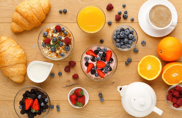 Continental breakfast with croissants and berries on natural wood - Stock Photo - Images
