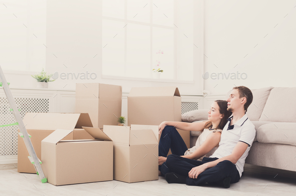 Young couple unpacking moving boxes - Stock Photo - Images